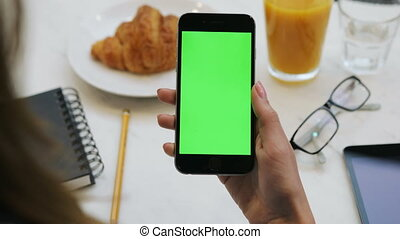 Woman using smartphone with green screen. Close-up video of woman's hands holding mobile phone. Chroma key. Vertical