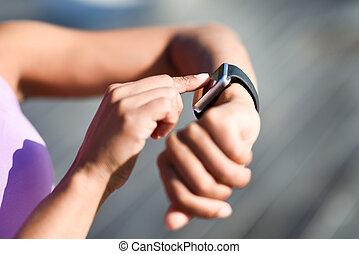 Woman using smartwatch touching touchscreen