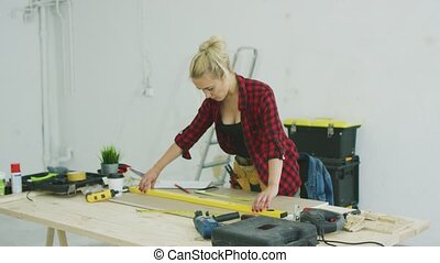 Woman using spirit level on workshop desk - Using bubble...