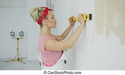 Woman using spirit level - Side view of attractive young...