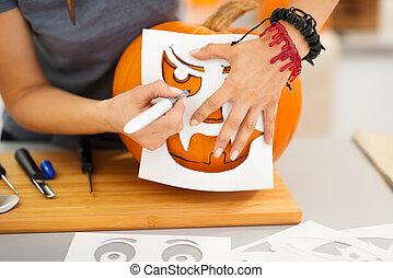 Woman using stencils to carve pumpkin Jack-O-Lantern....