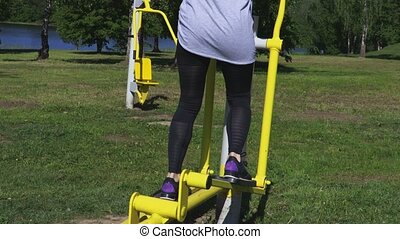 Woman using stepper training machine at park