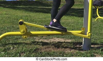 Woman using stepper training machine in park