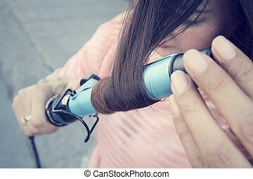 Woman using straightener with hair