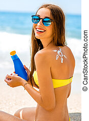 Woman using sun cream on the beach - Young woman with sun...