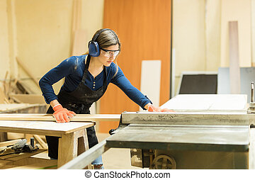 woodshop power tools. woman using table saw in a woodshop power tools