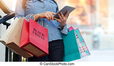 Woman using tablet and holding Black Friday shopping bag...