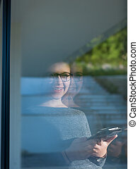 Woman using tablet at home by the window