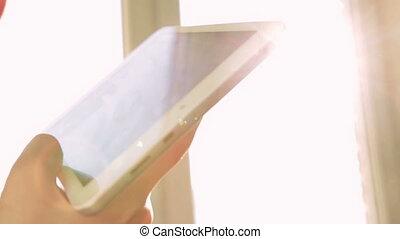Woman using tablet, bright sunlight