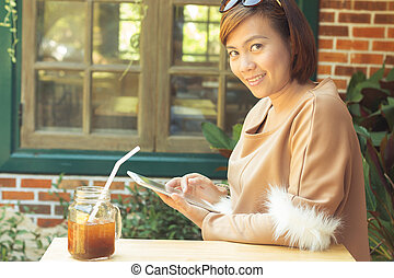 Woman using tablet computer and drinking coffee