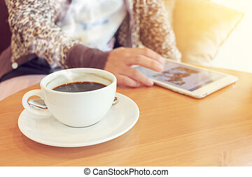 Woman using tablet computer and drinking coffee.