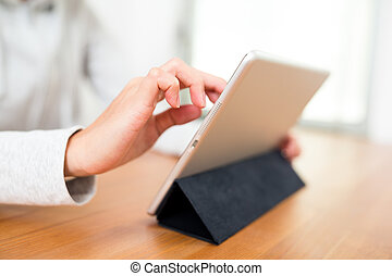 Woman using tablet computer at home