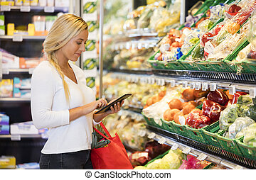 Woman Using Tablet Computer In Grocery Store - Smiling young...
