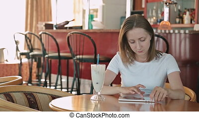 Woman using tablet computer touchscreen in cafe on cruise...