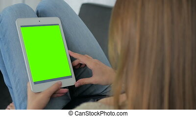 Woman using tablet computer with green screen - Woman using...