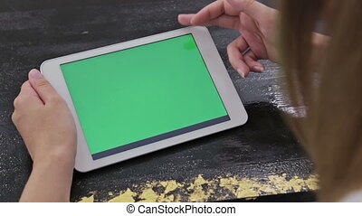 Woman using tablet computer with green screen
