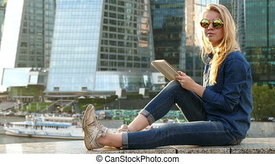 woman blonde using tablet computer on background of office buildings