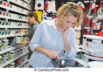 Woman using tablet in paint shop