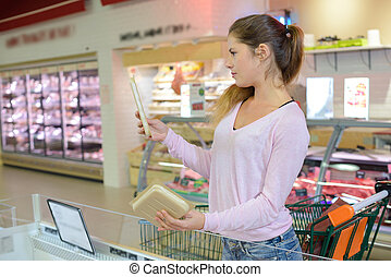 woman using tablet in supermarket