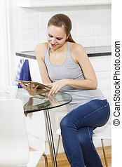 Woman using tablet in the kitchen - Woman drinking coffee...