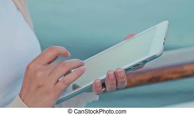 Woman using tablet on deck of cruise ship at sunrise