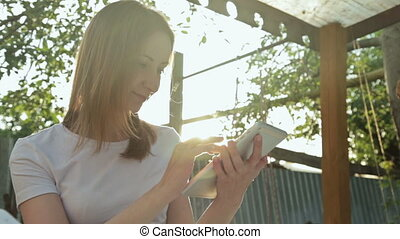 Woman using tablet PC at sunset