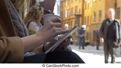 Woman using tablet PC in city street
