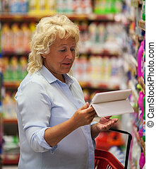 Woman using tablet PC in household chemicals section