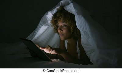 Woman using tablet under blanket - Charming young woman...