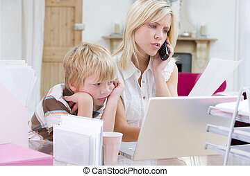 Woman using telephone in home office with laptop while young...