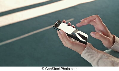 Woman using the mobile phone in the empty conference hall of cruise ship
