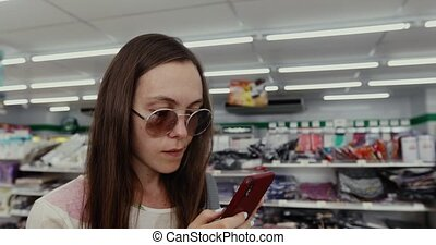 Woman Using the Phone in the Store