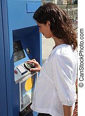 woman using ticket machine