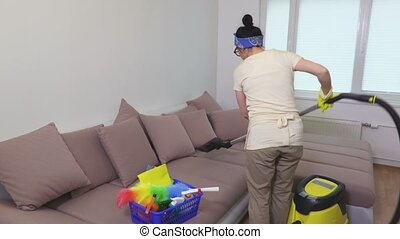 Woman using vacuum cleaner on sofa