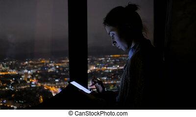 Woman using vertical black smartphone at night