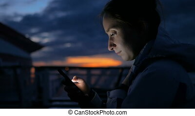 Woman using vertical smartphone on deck of cruise ship at night