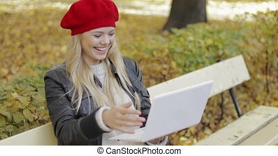 Woman using video chat app in park - Attractive woman in red...