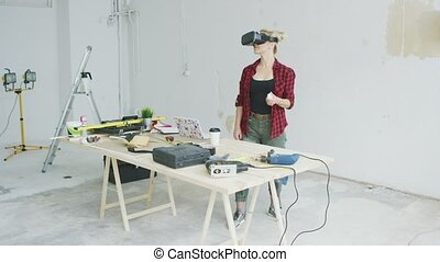 Woman using virtual reality goggles in workshop - Young...