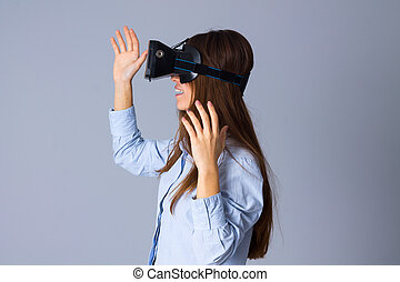 Woman using VR glasses - Young attractive woman in blue...
