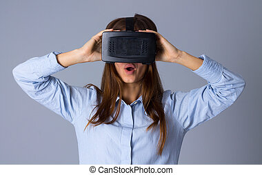 Woman using VR glasses - Young beautiful woman in blue shirt...