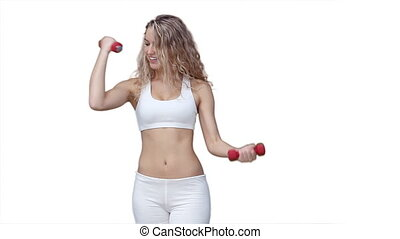 Woman using weights while training against a white ...