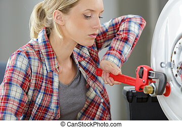 woman using wrench to undo nut