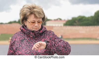 Woman using wristband fitness tracker outdoors