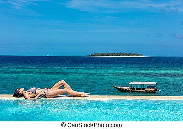 one caucasian woman enjoying vacations sunbathing on a infinity swimming pool by the seaside looking at the idian ocean Muyuni in Unguja aka Zanzibar Island Tanzania East Africa