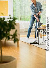 Woman vacuum carpet in house