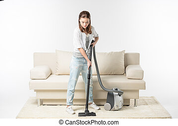 Woman vacuuming carpet - Concentrated beautiful young woman...