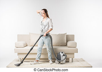 Woman vacuuming carpet - Tired young woman cleaning the...