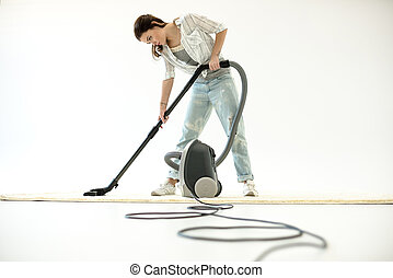 Woman vacuuming carpet - Young attractive woman cleaning...