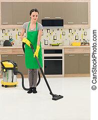 woman vacuuming kitchen floor - young woman vacuuming...