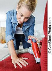 woman vacuuming sofa